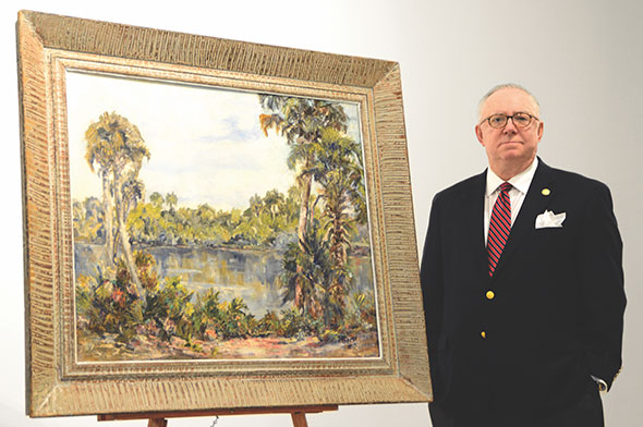 "Gary Libby stands next to ""Landscape South of Englewood, Florida,"" by Lois Bartlett Tracy (1901-2008). From the American Painting and the Florida School of Art – Selections from Private Collections exhibition at Stetson University in 2016. Photo courtesy of Stetson University Today."