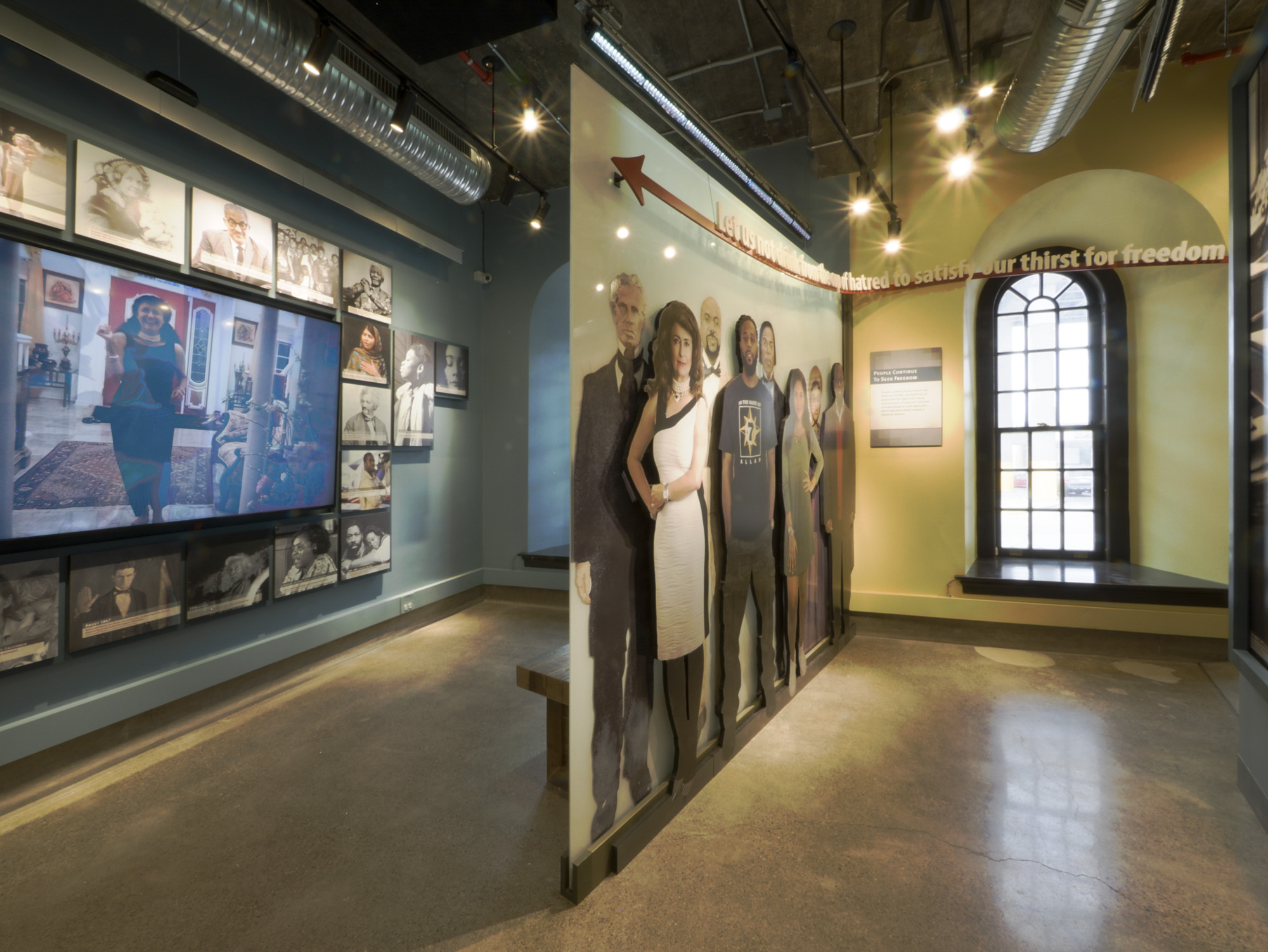 Figure 2. Gallery entrance showing life-size historical and contemporary figures. NiagaraFalls Underground Railroad Heritage Center, Freedom Gallery. Courtesy of Seth Frankel,Studio Tectonic.